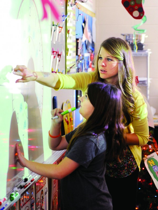 Tara Sorensen Kraft '08 works with a student in her 2nd grade room.