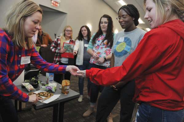 "Sara Shugar Fox, assistant professor of exercise science, hands out samples in the Adulting 101 session ""Real Food for Real Life."" This session featured healthy and simple recipes, tips for shopping and cooking for one and advice on packing affordable and healthy lunches."