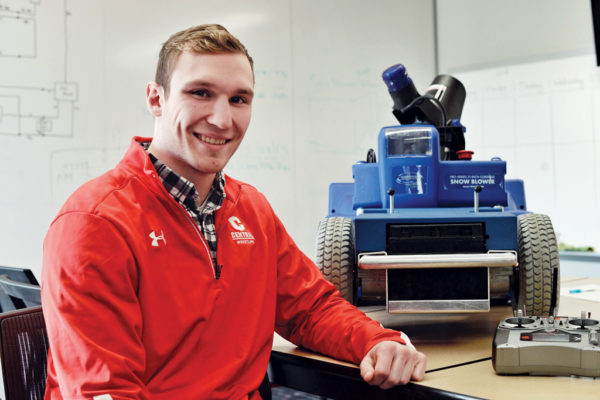 Cory McCleary '18 with the Ankle Biter, the robotic snow blower he designed and built with fellow engineering student Jacob Challen '18.