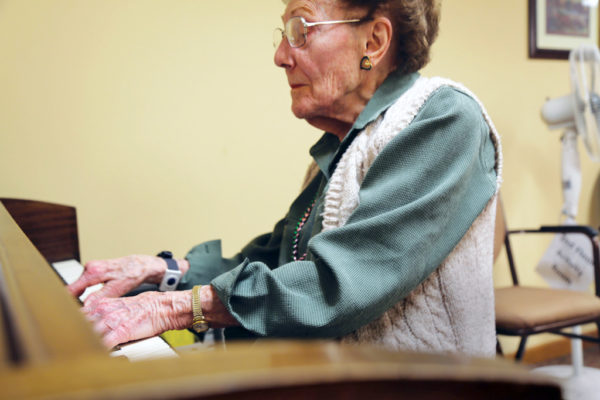 Van Zee plays the piano at her home in Newton.