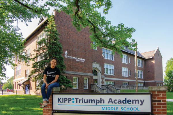 Carol Mendez '09 seated in front of St. Louis' KIPP Triumph Academy.