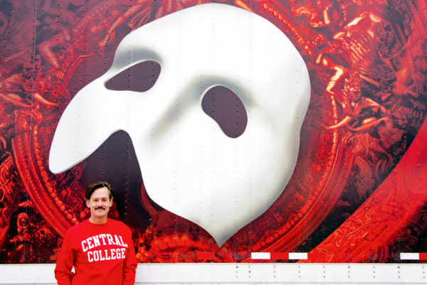 "Rob Lindley '95 standing beside a trailer advertising ""The Phantom of the Opera"""